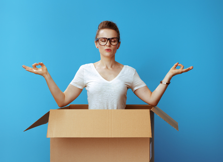 relaxed modern woman in white t-shirt doing yoga in a cardboard box against blue background