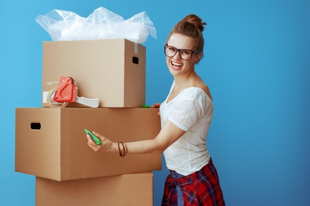 smiling modern woman in white t-shirt signs cardboard box isolated on blue background. woman labeling cardboard box with permanent marker. Stock Photo