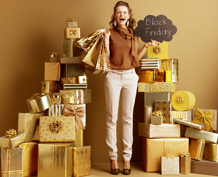 Full length portrait of smiling modern fashion-monger in gold beige pants and brown blouse with shopping bags and Black Friday sign rejoicing among 2 piles of golden gifts in front of a plain wall. Stock fotó