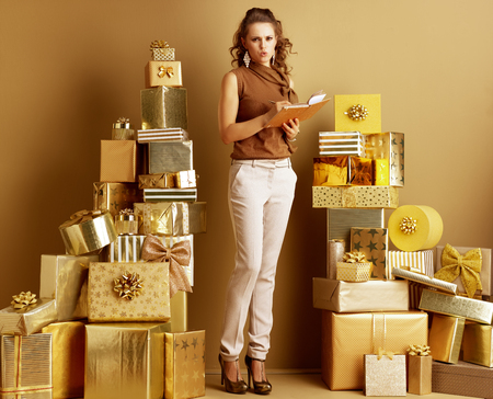 Full length portrait of tired modern woman in gold beige pants and brown blouse among 2 piles of golden gifts in front of a plain wall writing in a golden notebook. problem making list of gift ideas.