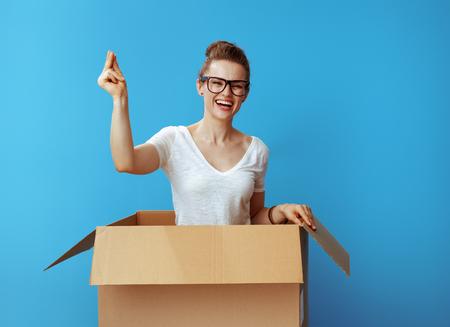 Heureuse femme moderne en t-shirt blanc avec des doigts claquant dans une boîte en carton isolée sur fond bleu