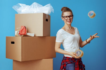 smiling young woman in white t-shirt near cardboard box throwing up adhesive tapes on blue background