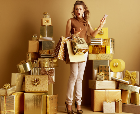 Disappointed stylish shopper woman in gold beige pants and brown blouse with shopping bags and smartphone among 2 piles of golden gifts. can't find a satisfying product from the current supply.
