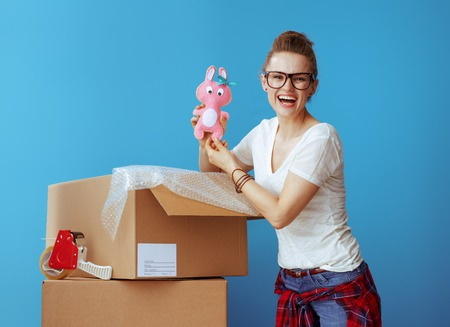happy modern woman in white t-shirt near cardboard box with old toy isolated on blue