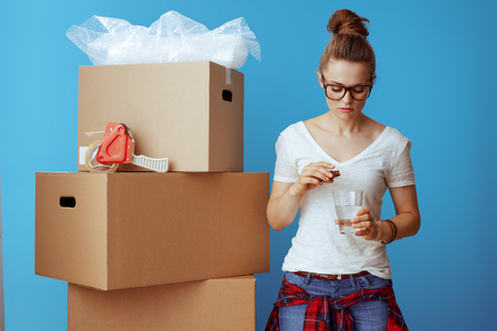 stressed young woman in white t-shirt near cardboard box drinking a sedative isolated on blue background Stok Fotoğraf