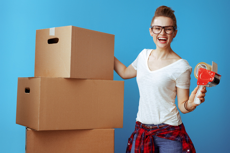 smiling young woman in white t-shirt near cardboard box with tape dispenser against blue background. Use packing and moving supplies to make work easier.
