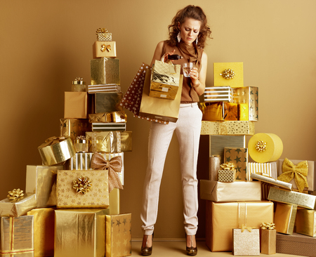 Stressed elegant fashion-monger in gold beige pants and brown blouse with shopping bags dripping sedative into a glass of water among 2 piles of golden gifts. problems of modern shopping concept. Stok Fotoğraf