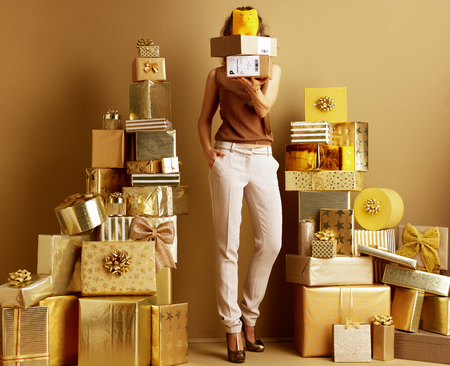 stylish woman in gold beige pants and brown blouse among 2 piles of golden gifts in front of a plain wall holding parcels and yellow piggy bank in the front of face. Free holiday shipping.