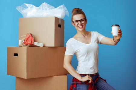 smiling modern woman in white t-shirt near cardboard box giving coffee cup isolated on blue background. Take a breather! Moving day is stressful, so take some time to relax.