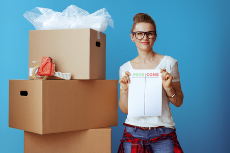 pensive modern woman in white t-shirt near cardboard box with pros cons list on blue background