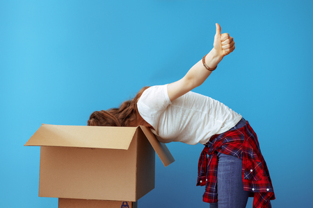 young woman in white t-shirt searching something in the cardboard box and showing thumbs up isolated on blue. Successful unpacking. Woman found missing item after long distance move.