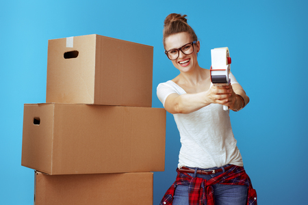 smiling young woman in white t-shirt near cardboard box using with tape dispenser as a gun isolated on blue. Stress free moving with professional packing and moving supplies.