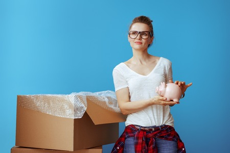 pensive modern woman in white t-shirt with piggybank against blue background. Moving on a budget. Stock Photo
