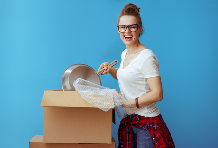happy modern woman in white t-shirt packing stuff isolated on blue background. get started packing with kitchen stuff first. Woman wrapping pan for extra cushioning.