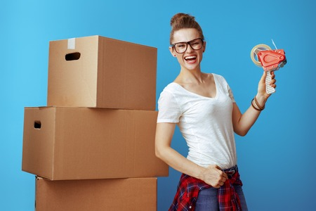 Portrait of smiling young woman in white t-shirt near cardboard box with tape dispenser against blue background. Use packing and moving supplies to make relocation a bit easier. Stock Photo