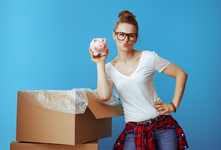 young woman in white t-shirt near cardboard box showing piggybank isolated on blue background. Economy way to move to location. Stock Photo