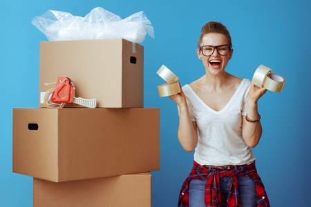 smiling young woman in white t-shirt near cardboard box showing adhesive tapes against blue background
