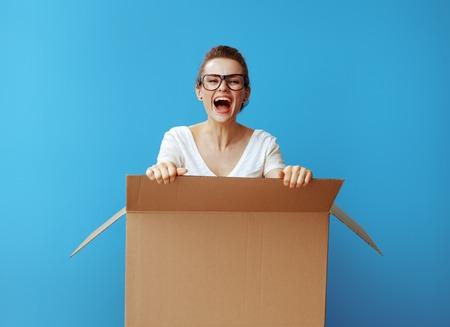 lächelnde junge Frau im weißen T-Shirt aus einem Karton vor blauem Hintergrund steigen