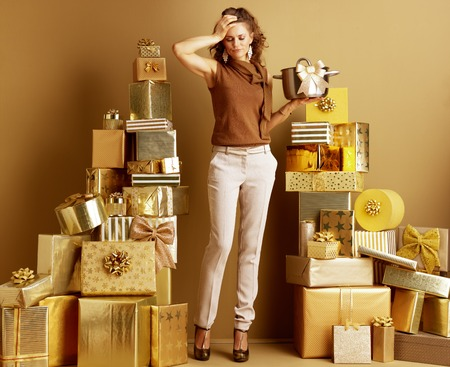 Full length portrait of stressed elegant shopper woman in gold beige pants and brown blouse with a stew pan with golden bow as a received gift among 2 piles of golden gifts in front of a plain wall.