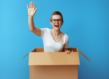 happy young woman in white t-shirt get out of a cardboard box and against blue background
