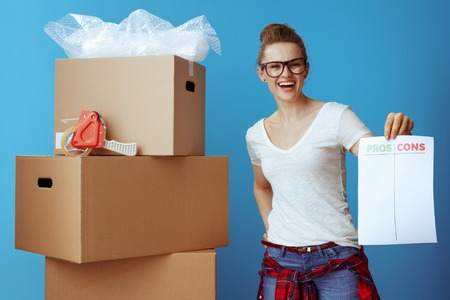 happy modern woman in white t-shirt near cardboard box showing pros cons list isolated on blue background
