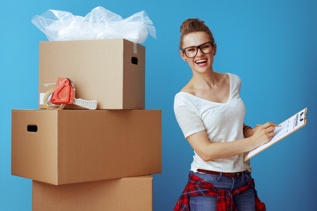 happy young woman in white t-shirt near cardboard box marking moving checklist against blue background