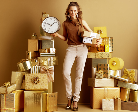 Full length portrait of happy modern woman in gold beige pants and brown blouse with parcels showing clock among 2 piles of golden gifts in front of a plain wall. Faster shipments and deliveries. 版權商用圖片