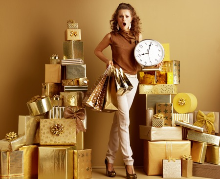 Full length portrait of surprised young woman in gold beige pants and brown blouse with shopping bags and clock among 2 piles of golden gifts in front of a plain wall. swiftness holidays shopping. 免版税图像