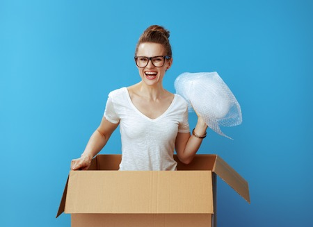 Portrait of smiling young woman in white t-shirt in a cardboard box with air bubble film packaging material against blue background