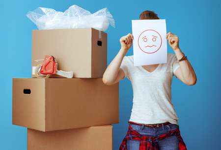 modern woman in white t-shirt near cardboard box hiding behind a sheet of paper with unhappy smiley isolated on blue Banco de Imagens