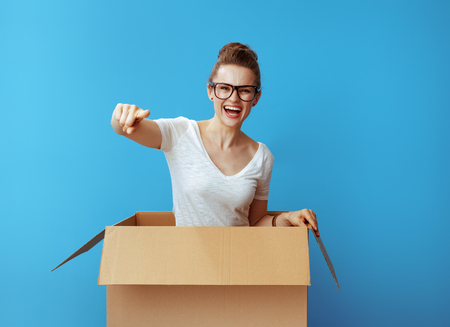 smiling young woman in white t-shirt in a cardboard box pointing in camera isolated on blue background