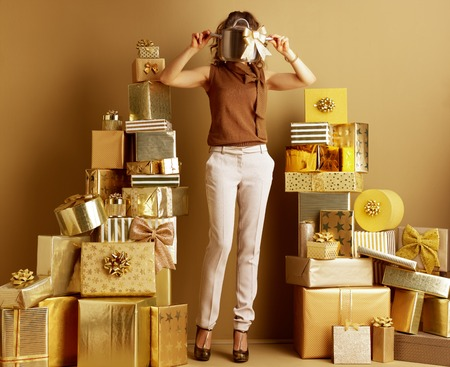 trendy woman in gold beige pants and brown blouse with a stew pan with golden bow as a received bad gift among 2 piles of golden gifts in front of a plain wall. Dont be a bad gift giver concept. Stock Photo
