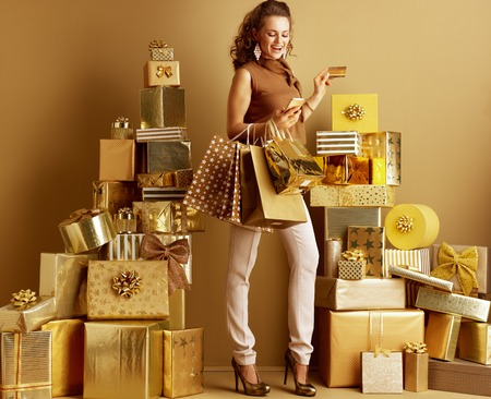 Stylish shopper woman in gold beige pants and brown blouse with shopping bags and golden credit card looking at smartphone among 2 piles of golden gifts. Mobile payments become a part of everyday life. Banco de Imagens