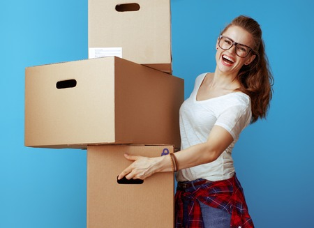 smiling modern woman in white t-shirt holding pile of cardboard boxes against blue background. transporting labeled cardboard boxes with belongings. Stock Photo