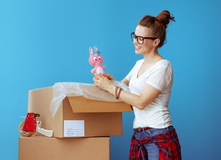smiling modern woman in white t-shirt near cardboard box looking at old toy against blue background