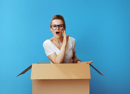 Jeune femme en t-shirt blanc dans une boîte en carton racontant des nouvelles passionnantes isolées sur fond bleu