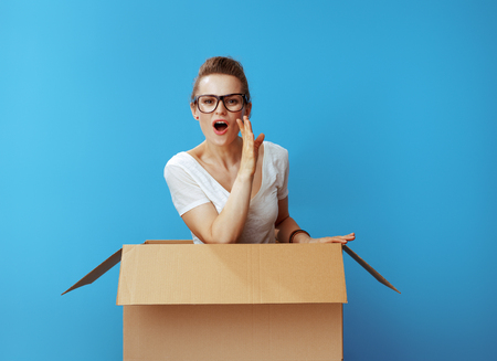 young woman in white t-shirt in a cardboard box telling exciting news isolated on blue background Stockfoto