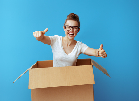 smiling modern woman in white t-shirt pops out of a cardboard box and showing thumbs up against blue background