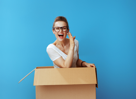 happy modern woman in white t-shirt in a cardboard box telling exciting news against blue background