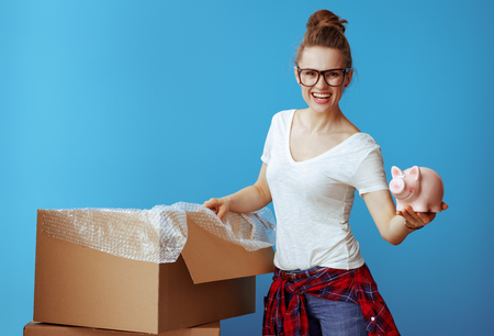 smiling young woman in white t-shirt showing piggybank on blue background. Dont overspend on packing supplies. Economy way to relocation.