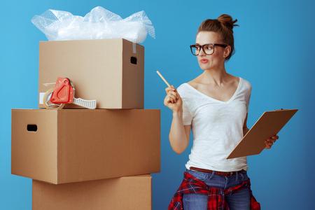 Mujer moderna en camiseta blanca cerca de la caja de cartón con lista de verificación en movimiento y recuento de cajas aisladas en azul Foto de archivo