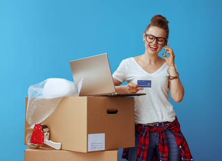 smiling modern woman in white t-shirt speaking on a cell phone near cardboard box with credit card and laptop on blue background Stock fotó