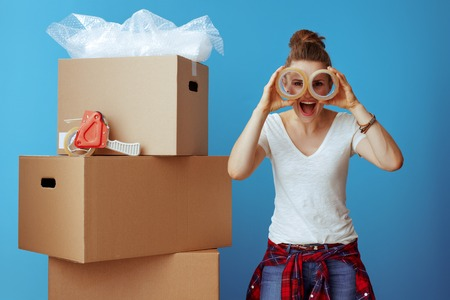 happy modern woman in white t-shirt near cardboard box looking through adhesive tapes isolated on blue