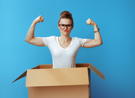 powerful young woman in white t-shirt showing biceps in a cardboard box against blue background