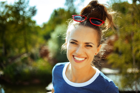 happy trendy solo tourist woman in blue t-shirt on river boat river cruising. Stok Fotoğraf