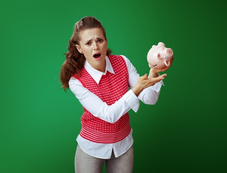 stressed young student woman in grey jeans and pink sleeveless shirt shaking pink piggy bank on chalkboard green background. Financial challenges and expenditures of modern education. Stock fotó - 117982524