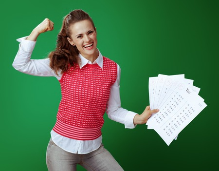happy fit learner woman in grey jeans and pink sleeveless shirt showing A+ test results and biceps isolated on green background.