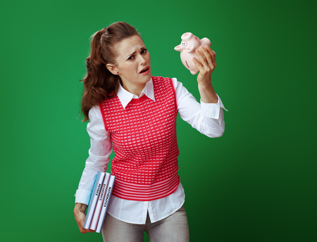 unhappy healthy student woman in grey jeans and pink sleeveless shirt with textbooks shaking pink piggy bank against green background. Financial challenges and expenditures of modern education.