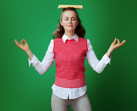 relaxed young learner woman in grey jeans and pink sleeveless shirt with a yellow book on head doing yoga on green background. Stress free education