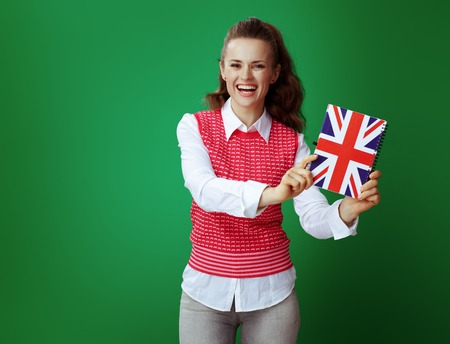 smiling healthy student woman in grey jeans and pink sleeveless shirt showing United Kingdom flag coloured notebook isolated on green. English language courses or stationary promotion.